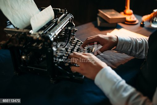 655113470istockphoto Literature author in glasses typing on typewriter 655113470