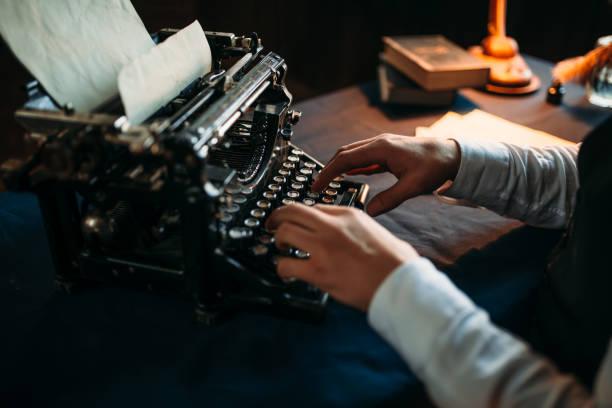 Autor de literatura em copos digitando na máquina de escrever - foto de acervo
