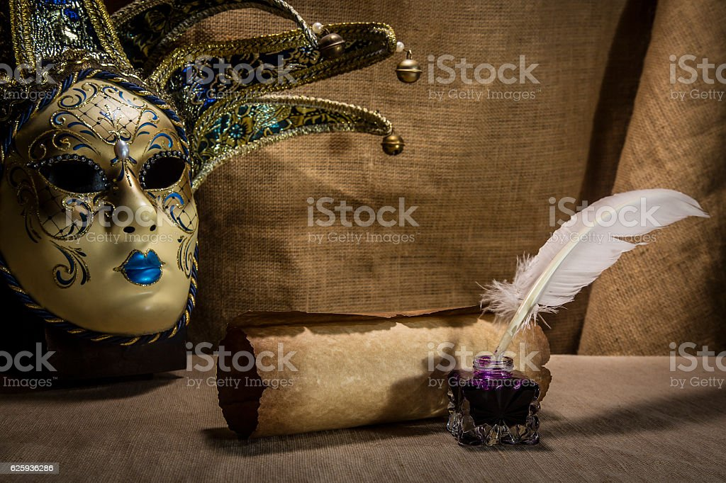 Literature concept. Old inkstand with feather near venezian mask stock photo