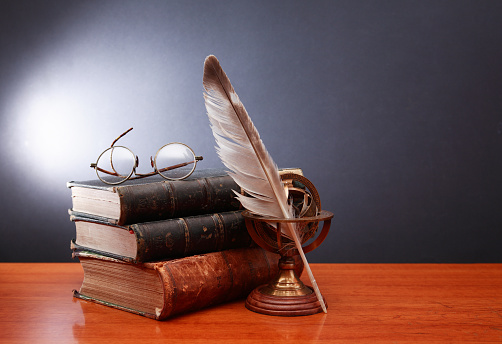 Vintage still life with quill pen near book and spectacles on dark background