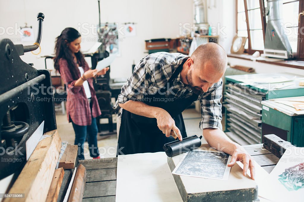 Lithography workers creating pattern at workshop stock photo