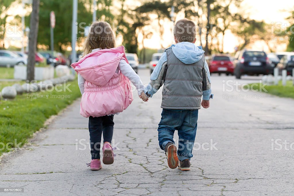 Litle boy and girl walking together and holding hands stock photo