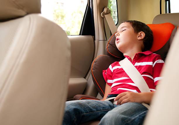 culotte courte garçon dort dans un siège de voiture coffre-fort - child car sleep photos et images de collection
