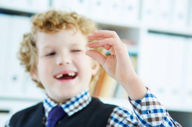 Litle kaukasischen junge hält eine Tiefe Taille Milchzahn zwischen seinen Fingern und lacht. – Foto