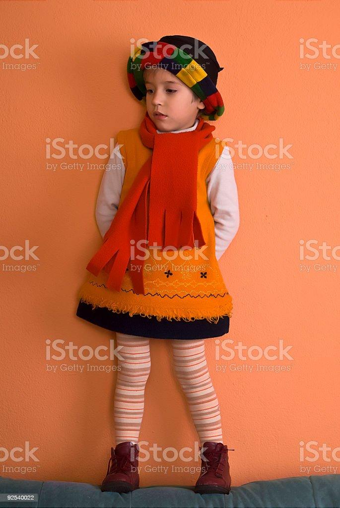 Litle Girl in orange dress looking royalty-free stock photo