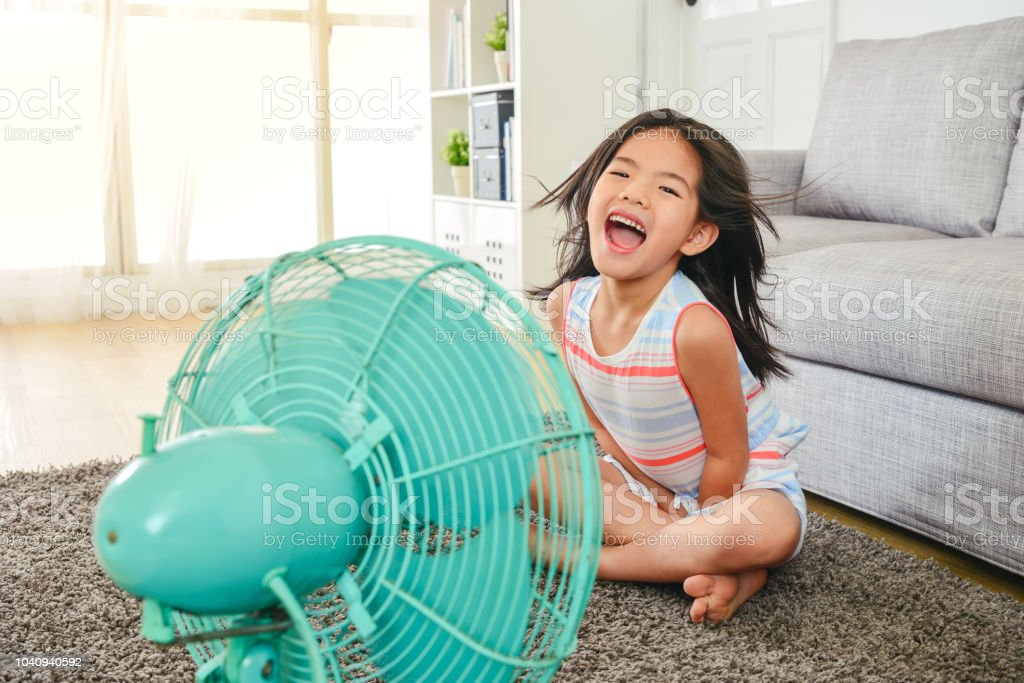 litle girl laughing and sitting in front of fan. royalty-free stock photo