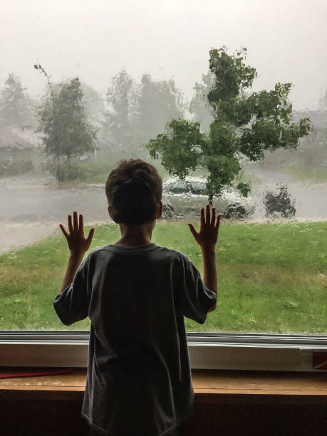 litlle boy seen from behind and looking at the rain storm through living room window - boy looking out window stock pictures, royalty-free photos & images