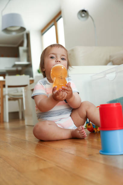 Litlle boy sitting on the floor playing with toys stock photo