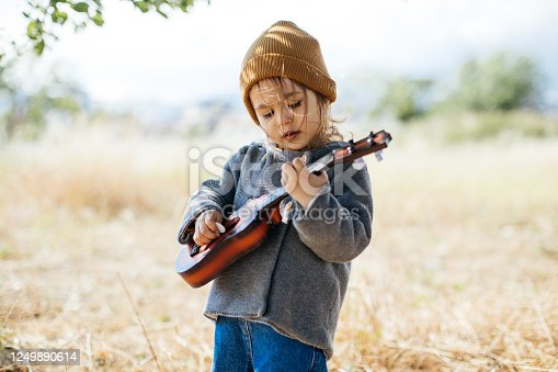 Adorable boy with guitar, standing on the grass. Toddler girl playing guitar at sunny countryside home garden