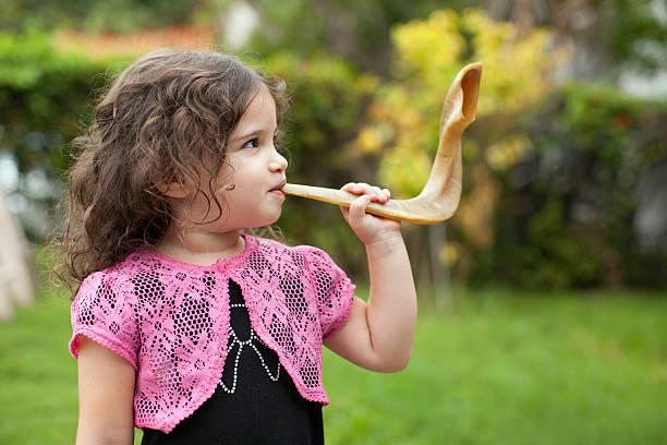 Litlte girl blowing Shofar stock photo