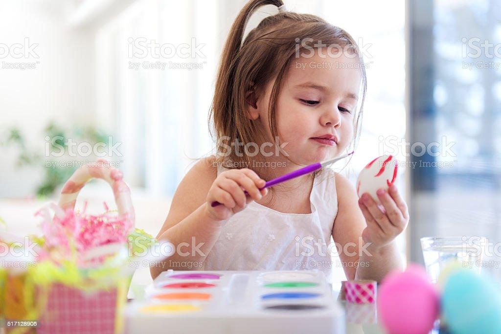 Litte girl painting easter eggs stock photo