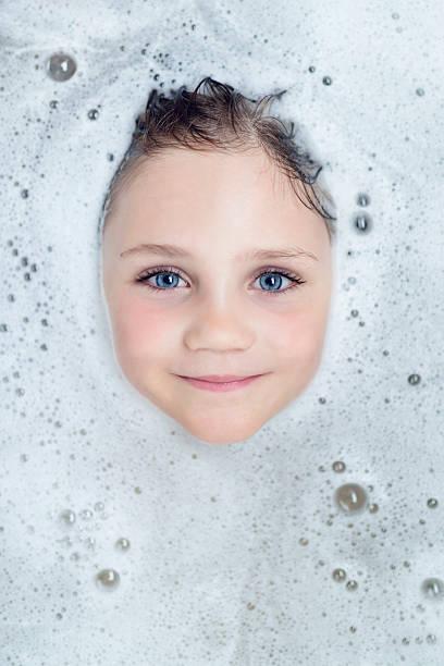 wenig blondes mädchen look durch bad-schaum - kinderbadewanne stock-fotos und bilder