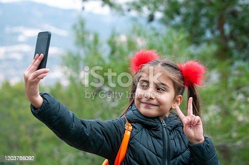 Little girl taking selfie her mobile phone by garden