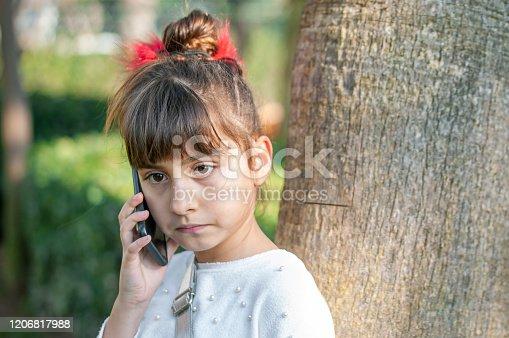 Little girl using her mobile phone by garden