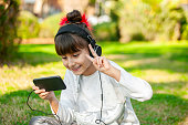 Little girl looking her mobile phone with headset outdoor