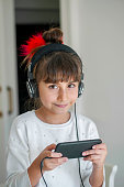 Little girl looking her mobile phone with headset