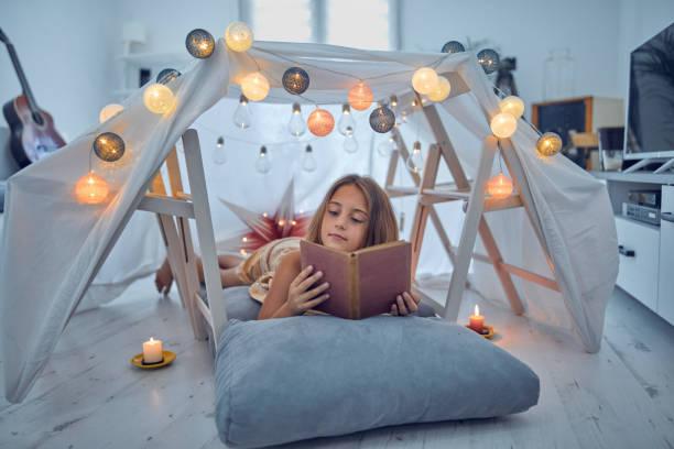 Kleines 10-jähriges Mädchen liest klassisches Buch unter ihrem selbstgebauten Zelt im Wohnzimmer. – Foto