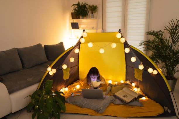 Kleines 11-jähriges Mädchen mit Laptop unter ihrem hausgemachten Zelt im Wohnzimmer. – Foto