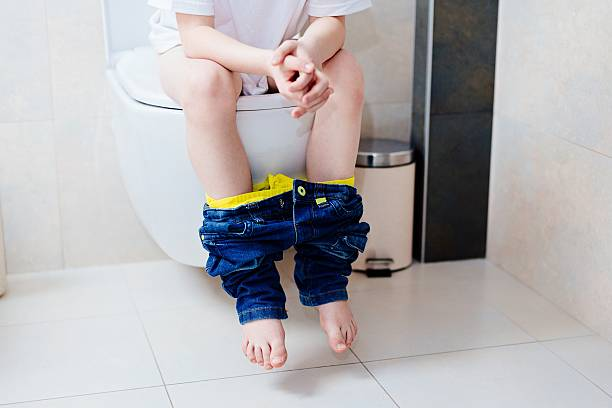 little 7 years old boy on toilet. - kinder wc stock-fotos und bilder