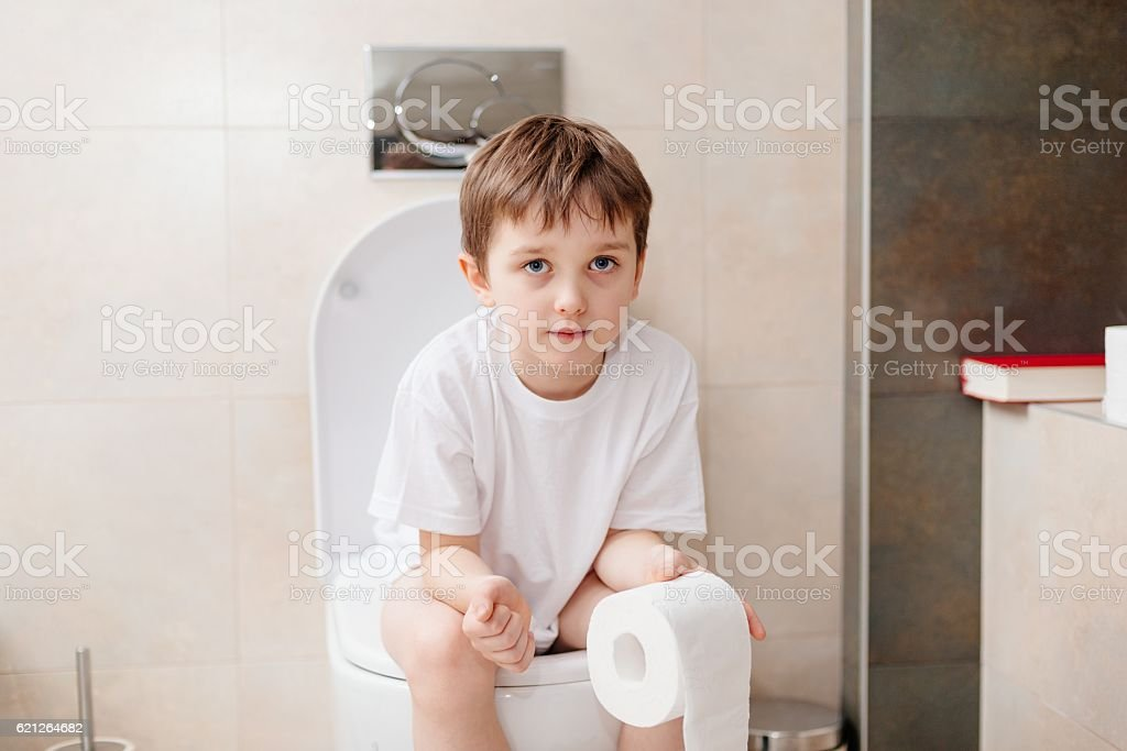little 7 years old boy sitting on toilet おまるのストックフォトや