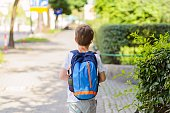 Little 7 years schoolboy going to school.