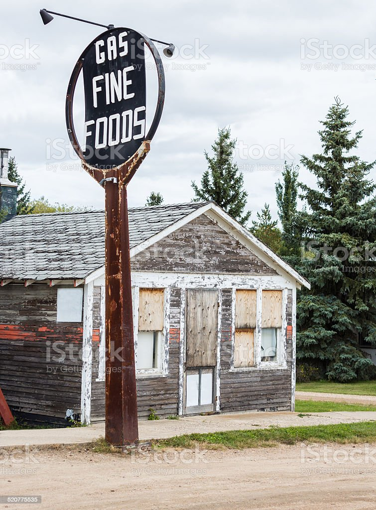 little abandoned wood store with with tall metal sign. stock photo