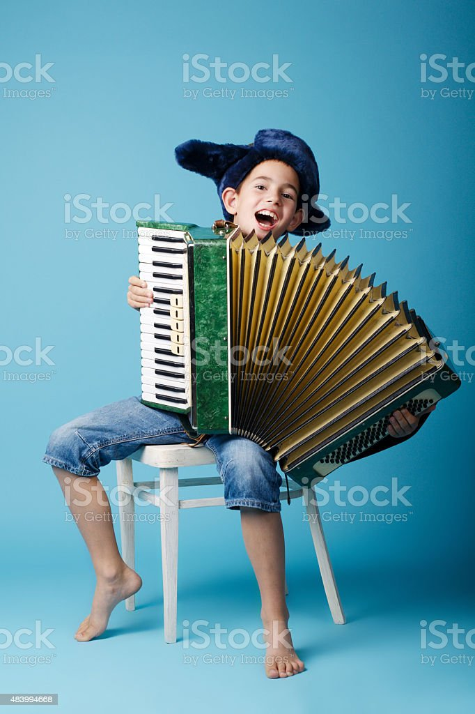 little accordion player on blue background stock photo