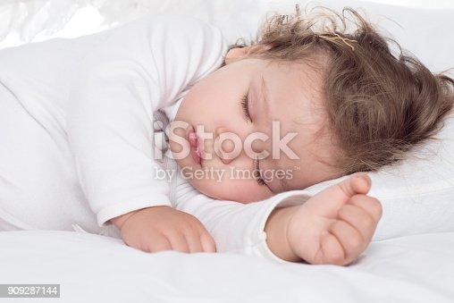 istock little adorable baby girl sleeping on bed 909287144