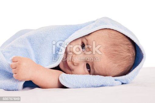 626089510 istock photo Little adorable baby lying on bed under blue towel 535767649