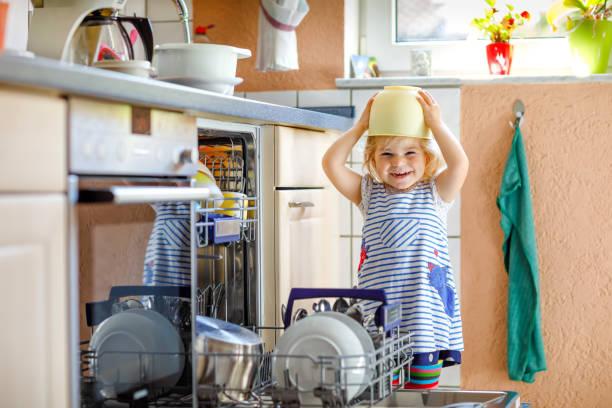 Kleines entzückendes Kind hilft, Spülmaschine zu entladen. Lustige glückliche Kleinkind Mädchen in der Küche stehen, halten Geschirr und setzen eine Schüssel auf den Kopf. Gesundes Kind zu Hause – Foto