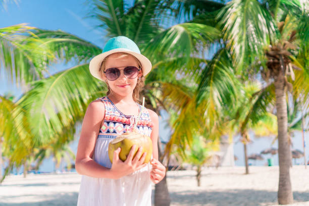 d12bb8a3c2c06 Little adorable girl with big coconut on white sandy beach stock photo