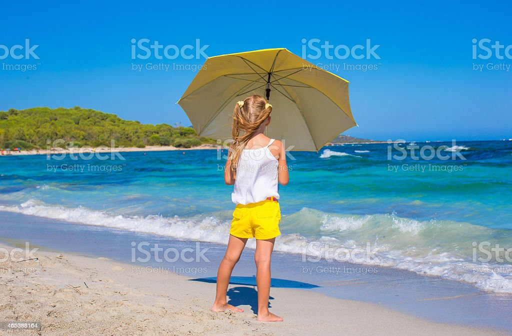 3c692ba85161a Little adorable girl with big yellow umbrella on tropical beach royalty-free  stock photo