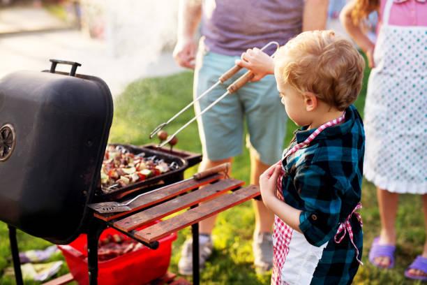 kleinen entzückenden kleinkind jungen nutzt koch clip, um seine eltern zu helfen, mit dem grill. - kindergrill stock-fotos und bilder