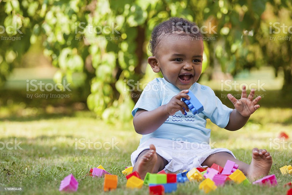 Little african american baby boy playing in the grass royalty-free stock photo