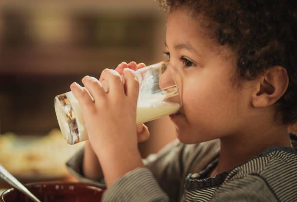 小非洲裔美國男孩從玻璃杯裡喝鮮牛奶。 - 牛奶 個照片及圖片檔