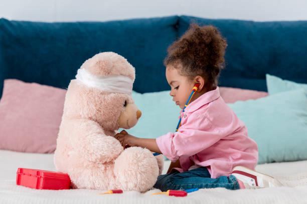 Afrikanische amerikanische Kind in rosa Jacke spielt des Arztes mit Teddybär – Foto