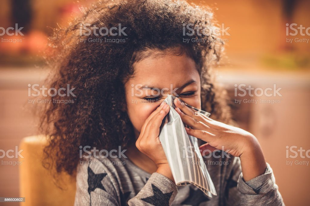 Little African American girl blowing nose with a napkin. stock photo