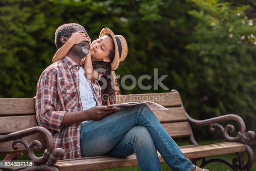 istock little african american girl closing eyes of her grandfather sitting on bench in park 834337118