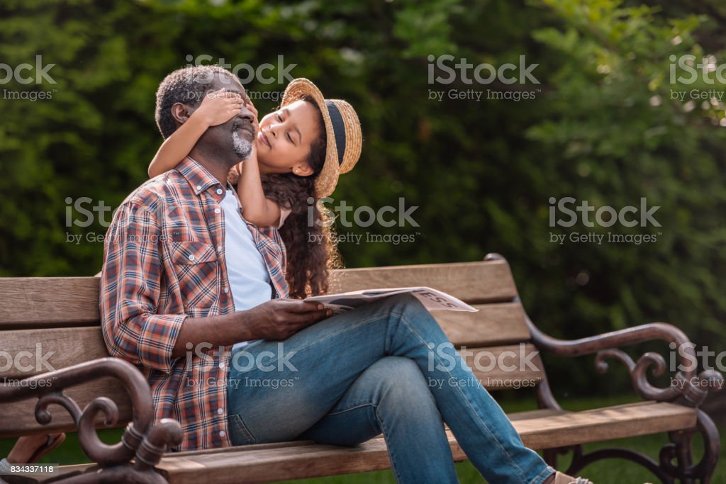little african american girl closing eyes of her grandfather sitting on bench in park stock photo