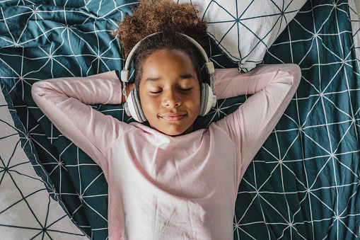 Young girl laying in bed enjoying music, she is listening to music via wireless headphones