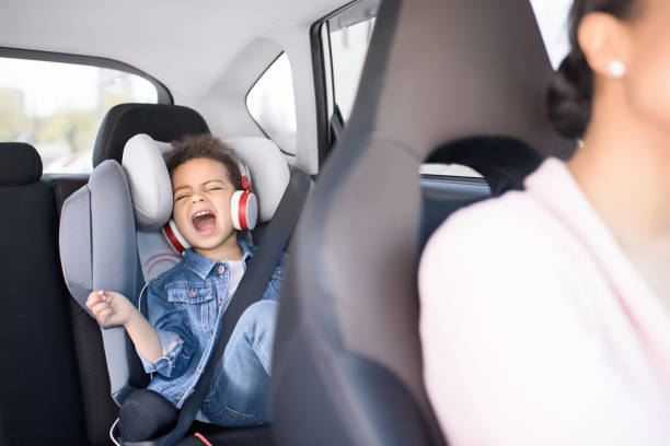 little african american girl listening music with mother sitting in car - singing stock photos and pictures