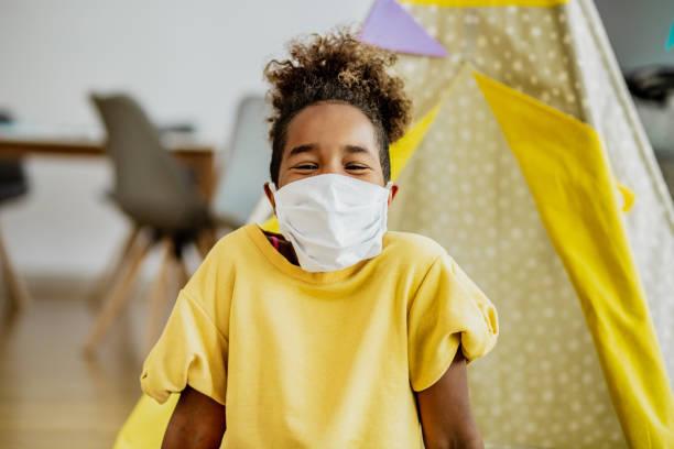 petite fille afro-américaine souriant avec le masque intérieur - masque enfant photos et images de collection