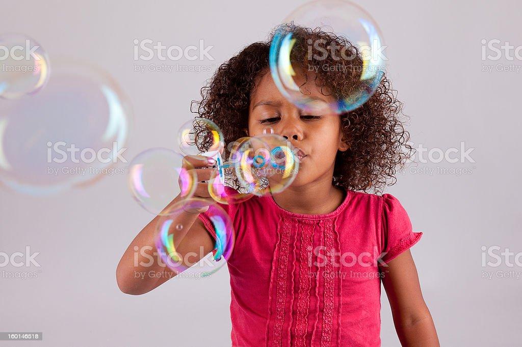 Poco Chica asiática africana Soplando burbujas de jabón - foto de stock