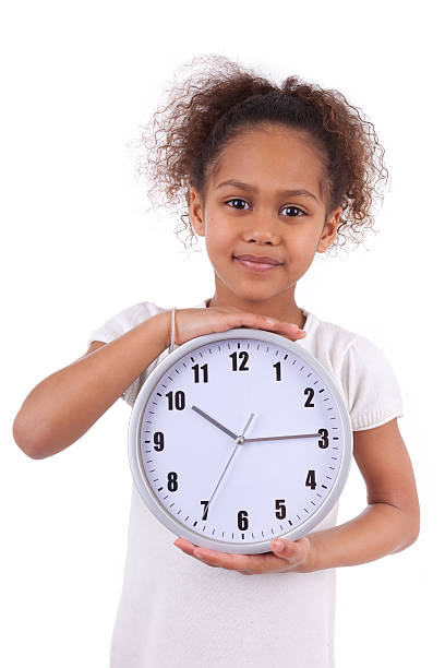 Little african asian girl holding a  clock stock photo