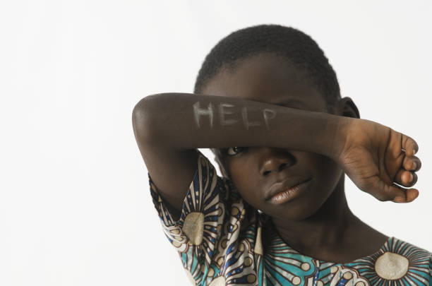 Little African boy asks for help by covering his face with his arm, isolated on white stock photo