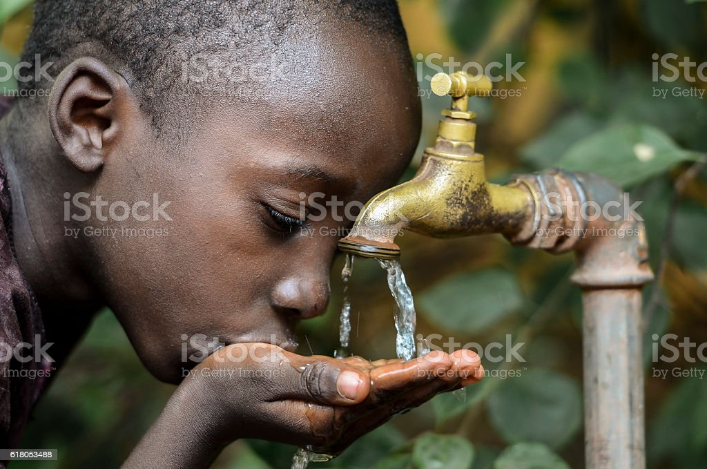 Little African Boy Drinking Healthy Clean Water from Tap stock photo