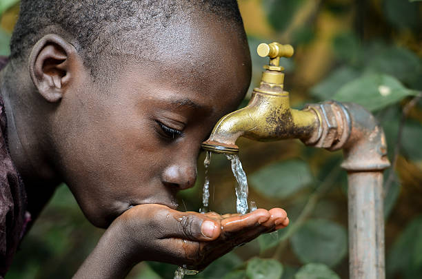 little african boy drinking healthy clean water from tap - somalia stock photos and pictures