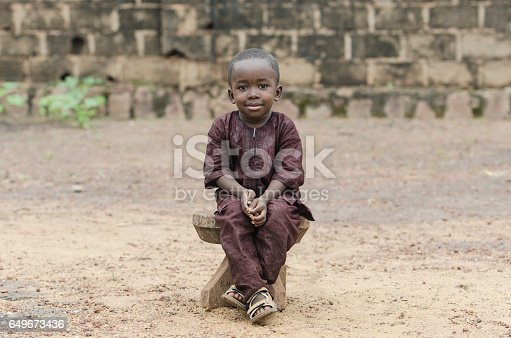 istock Little African Boy Sitting Outdoors posing with a big Smile on his Face 649673436