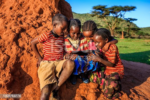 Little African children using digital tablet in the village in Southern Ethiopia, Africa. Children are sitting on termite's mound.