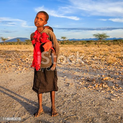 Little African girl from Samburu tribe carrying her baby brother, Kenya, Africa. Samburu tribe is one of the biggest tribes of north-central Kenya, and they are related to the Maasai.